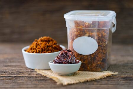Spicy chili paste in white ceramic and plastic containers on wood background