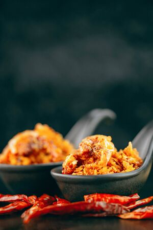 Spicy crispy shrimps chili paste in black spoon on dark background