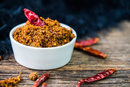 Spicy dried fishes chili paste with white ceramic container on wood background