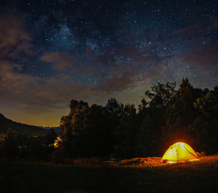 A camping tent is under milky way sky and twilight at night in Horseshoe Canyon Ranch, Jasper Arkansas. Stock Photo
