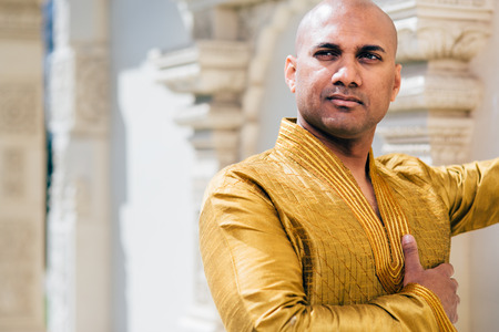 The handsome Indian man wears a gold kurta and posed at a temple.