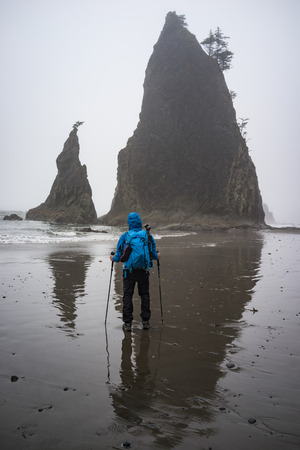 This is the picture of a male hiker with blue jacket and back pack standing on the sand and looking at Rialto Beach, Olympic National Park, Washington.