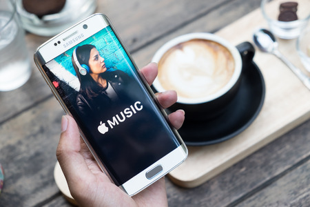 android: CHIANG MAI, THAILAND - NOV 20, 2015: A man hand holding screen shot of Apple music app showing on samsung galaxy s6 edge. Apple Music is a beta version on android.