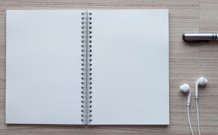hoja en blanco: lápiz negro, tapones para los oídos y el cuaderno abierto en madera.