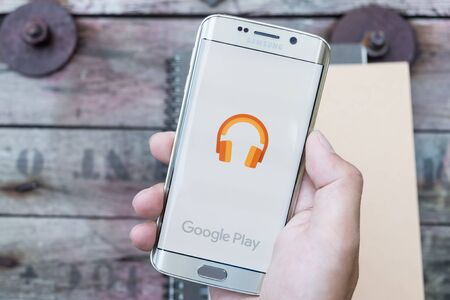 google play: CHIANGMAI, THAILAND -NOV 28, 2015, A man hand holding screen shot of google play music . Google play music is the most interesting and a user friendly app to listen to music.