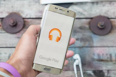 google play: CHIANGMAI, THAILAND -NOV 28, 2015, A man hand holding screen shot of google play music on samsung galaxy s6 edge. Google play music is the most interesting and a user friendly app to listen to music.