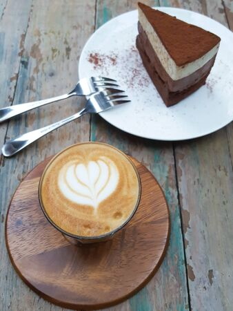 A Cup of hot latte art coffee and delicious chocolate cake on wooden table Stock Photo