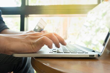 cvv: Online payment,Mans hands holding a credit card and using laptop for online shopping
