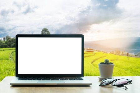 terraced field: laptop with blank screen on wood table with Terraced rice field on Mountain background