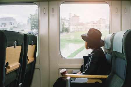 Enjoying travel. Young pretty woman traveling by the japan classic train sitting near the window. vintage filter. Banco de Imagens - 80125885