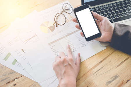 business documents on office table with smart phone and laptop computer and graph financial diagram vintage filter