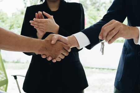 Estate agent shaking hands with his customer after contract signature and congratulation