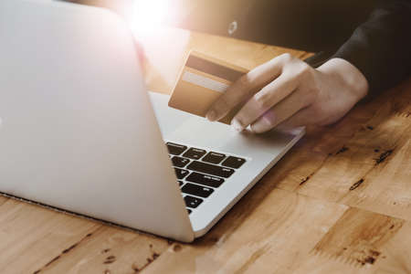 electronic commerce: Close up hand of woman holding credit card and using laptop computer. Online shopping concept with vintage filter tone