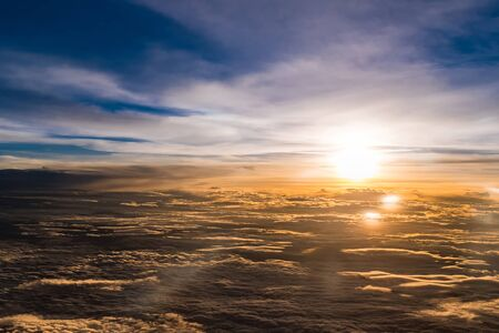 arial view: Aerial view from airplane flying above the clouds , Twilight time with sunset flare