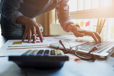 Księgowi pracują analizując sprawozdania finansowe na laptopie w swoim biurze, koncepcja biznesowa