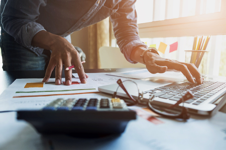 Los contadores trabajan analizando informes financieros en una computadora portátil en su oficina, concepto de negocio