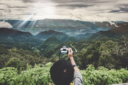 Enjoy travel with peak of mountain. A backpacker hand holding a digital camera at peak of mountain to take a photo of panorama mountain view with sunset light rays