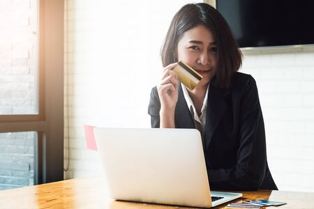 Enjoy with online shopping. Smart asian woman holding credit card and using laptop computer. Online shopping concept