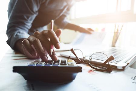 Feche acima da pena de terra arrendada da mão do homem de negócios ou do contabilista que trabalha na calculadora para calcular dados do negócio, original da contabilidade e laptop no escritório, conceito do negócio