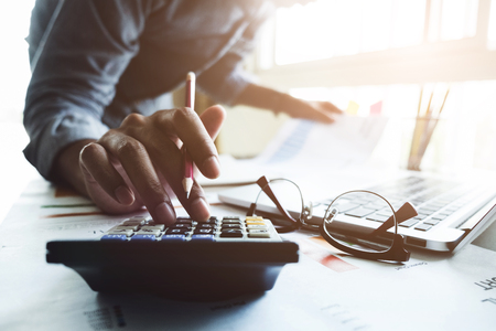 Close up of businessman or accountant hand holding pen working on calculator to calculate business data, accountancy document and laptop computer at office, business concept