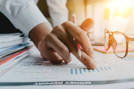 Close up of Business woman investment consultant analysis company annual financial report balance sheet statement working with documents graphs. Concept picture of economy, market, office, money and tax.