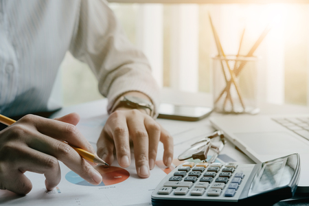 Close up of businessman or accountant hand holding pen working on calculator to calculate business data