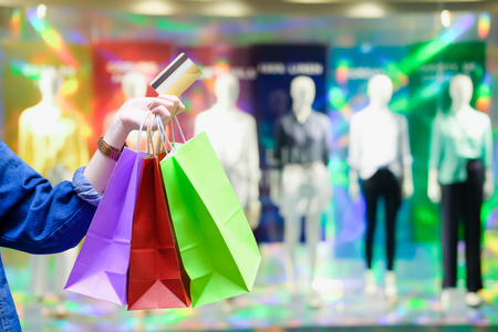Woman with shopping bags with colourful and creditcard with cloth shop background - Shopping credit card payment concept 版權商用圖片