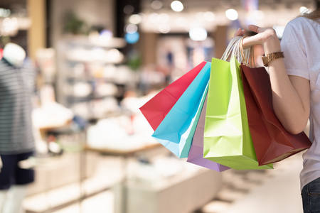 Young woman with shopping bags over shopping mall background - happiness, consumerism, sale season concept