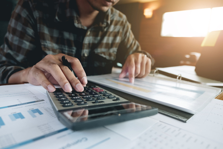 businessman working with calculator for financial document in office. male accountant doing accounting and calculating. bookkeeper making calculation. Savings, finance 版權商用圖片