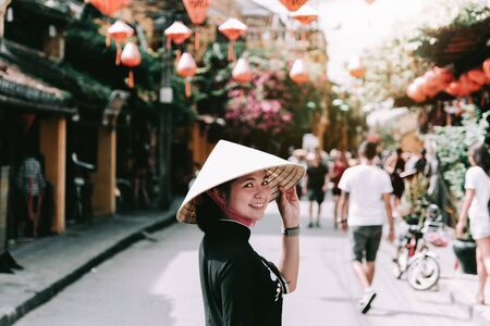 Beautiful girl wearing vietnam hat or Non La and sightseeing at Heritage village in Hoi An city in Vietnam Imagens