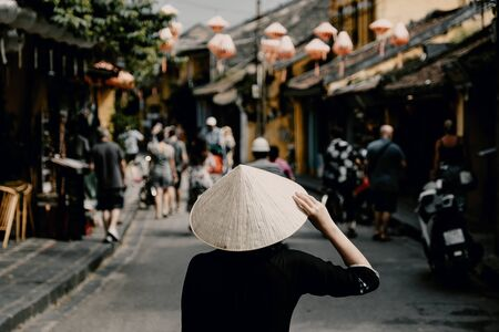 Tourist woman wearing vietnam hat or Non La and sightseeing at Heritage village in Hoi An city in Vietnam
