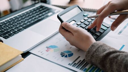 business woman working with calculator, business document and laptop computer notebook in office.