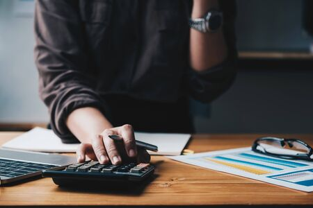 Business woman entrepreneur using a calculator with a pen in her hand, Foto de archivo