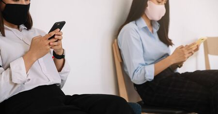 Two Asian young woman chatting in smartphone and wearing mask sitting distance protect from COVID-19 viruses for social distancing for infection risk.