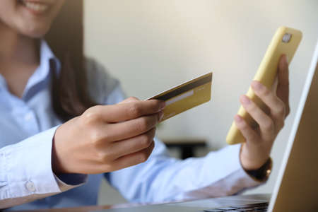 Close up hand of woman holding credit card and using laptop computer at home. Online shopping concept.