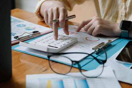 Accountant or banker calculate the financial report with calculator Фото со стока