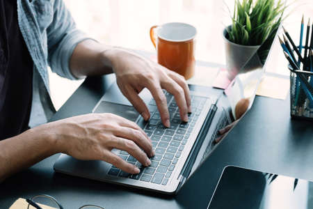 Close up businessman using laptop computer at home Фото со стока