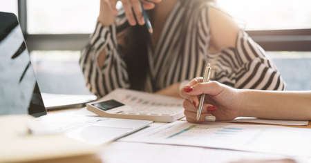 Close up of businessman or accountant working on calculator to calculate business data, accountancy document at meeting room