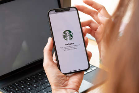 Chiang Mai, Thailand : Mar 7 2021 : A woman holds iPhone 12 showing Starbucks logo on screen in Starbucks coffee shop. Editorial