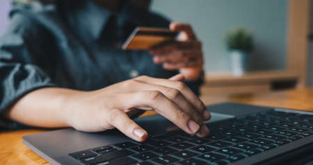Close up woman at home shopping online with credit card and laptop computer