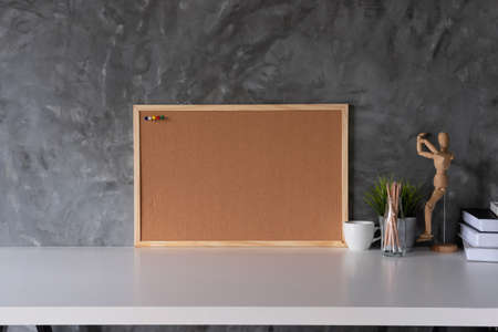 White working space with Cork board and cup, office supplies and book in home office workplace