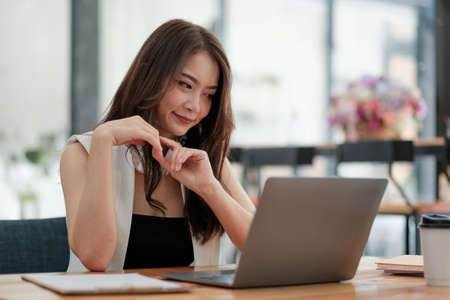 Portrait of attractive asian business woman working with laptop computer for group online meeting conference,