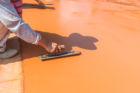 concrete surface finishing: Close-up of hand using trowel to finish wet concrete floor