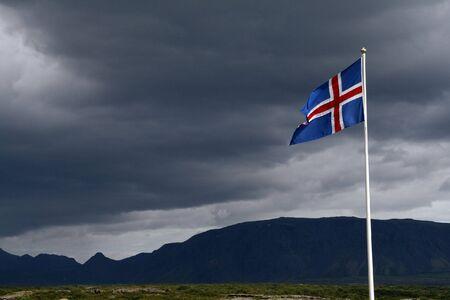 Iceland flag on the bacground of a stromy sky over the Thingvellir National Park
