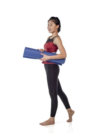 Young woman holding her yoga mat isolated on white background