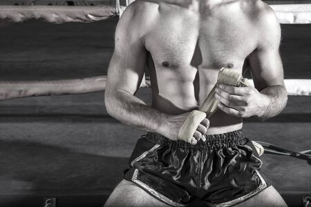 Close-up of hand boxer pulls wrist wraps before the fight, black and white tone color Archivio Fotografico