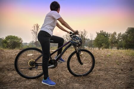 woman riding bicycle on the sunset in the park.