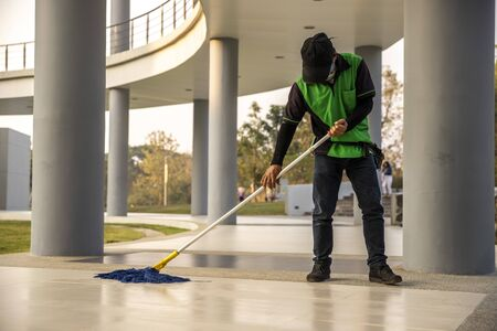 A  janitor man  cleaning  mopping floor in office building or walkway modern building.  A janitor man with broom cleaning office corridor