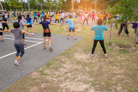 People exercising with dance aerobics at public Park. Aerobics is a popular fitness activity in SE Asia, often held in public parks.