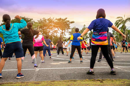 People exercising with dance aerobics at public Park. Aerobics is a popular fitness activity in SE Asia, often held in public parks. Standard-Bild